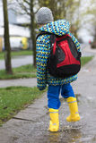 Child in rain boots walking in puddle Stock Images