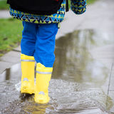 Child in rain boots walking in puddle Royalty Free Stock Photo