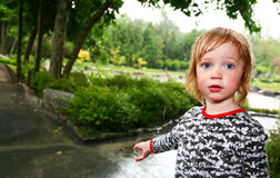 Child rain wet. Child in rain soaked with water. wet kid caught in storm in park or garden Stock Image