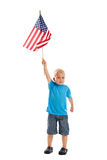 Child raising flag. A 3 year old boy raising an American flag isolated on white Stock Photos