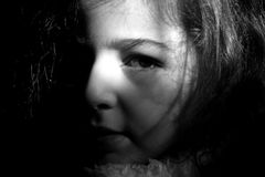 A child. Ray of light on the face of a small woman stock photography