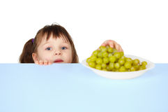 Child reaches for grapes lying on table Royalty Free Stock Photo