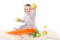 Child reaches out a green apple and smiling Royalty Free Stock Photos