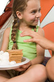 Child reaching for plate of treats Stock Photos