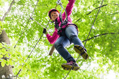 Child reaching platform climbing in high rope course. Women reaching platform climbing in high rope course Stock Image