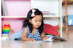 Child read, cute little girl reading a book and lying on floor Royalty Free Stock Image