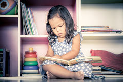 Child read, cute little girl reading a book and sitting on floor Stock Photos