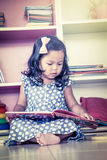 Child read, cute little girl reading a book and sitting on floor Royalty Free Stock Photos