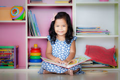 Child read, cute little girl is smiling and reading a book Royalty Free Stock Image