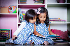 Child read, two cute little girls reading book together on books Stock Images