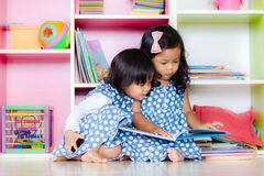 Child read, two cute little girls reading book together. On bookshelf background Royalty Free Stock Photography