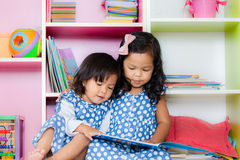 Child read, two cute little girls reading book together. On bookshelf background Stock Image