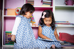 Child read, two cute little girls reading book together. On bookshelf background Stock Images