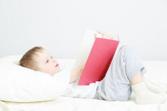 Child reading in bed Stock Photo