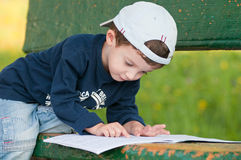 Child reading on a bench. Child white cap reading on a bench Stock Image