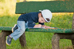 Child reading on a bench Royalty Free Stock Photos