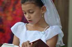 Child reading bible in enjoyment Stock Photo