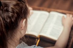 Child Reading Bible. Child Girl Reading the Book Bible stock images