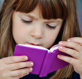 Child reading book. Close up shot of a pretty young girl reading a book with interest royalty free stock photo