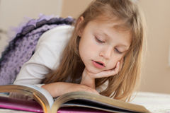 Child reading a book. Portrait of a little girl reading a book Royalty Free Stock Image