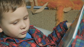 Child reading a book. Baby in pajamas. stock video