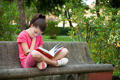 Child reading a book. On a bench Stock Photography