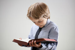 Child reading a book or bible. Boy studying and reading a book or bible isolated concept for education, religion or homework Stock Photography