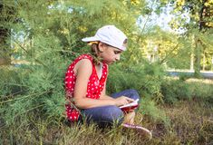 Child reading book or bible outdoors . Cute little girl reading the Bible . royalty free stock photo
