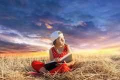 Child reading book or bible outdoors . Young Child`s Hands Praying on Holy Bible . stock photos