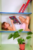 Child reading a book in a bookcase Royalty Free Stock Image