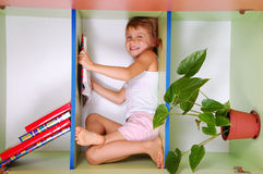 Child reading a book in a bookcase. Smiling little girl lying on a bookshelf and reading royalty free stock photography