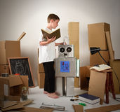 Child Reading Book and Building Cardboard Robot. A child is reading a book and building a metal robot from cardboard boxes on white for an imagination, science Royalty Free Stock Photography