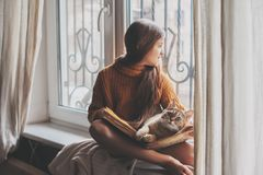Child reading a book with cat. Child in warm woolen sweater seating on window sill and reading a book. Winter weekend with cat at home. Cozy scene, hygge concept Royalty Free Stock Photography