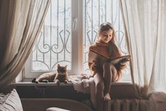 Child reading a book with cat stock photos
