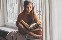 Child reading a book with cat. Child in warm woolen sweater seating on window sill and reading a book. Winter weekend with cat at home. Cozy scene, hygge concept Stock Photo