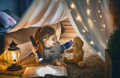 Child is reading a book. Cute little child is reading a book with flashlights in tent. Happy girl playing at home. Funny lovely kid having fun in room royalty free stock image