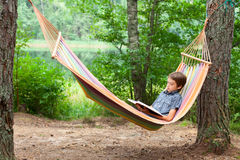 Child reading book in hammock. Boy lying in hammock reading a book outdoors Stock Photos