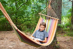 Child reading book in hammock. Boy lying in hammock reading a book outdoors Stock Photography