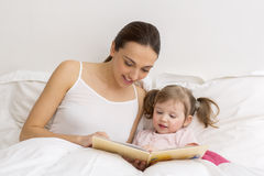 Child reading a book with her mother Royalty Free Stock Photos