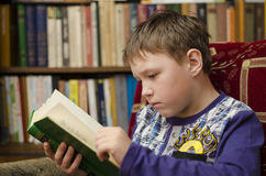 Child reading book at home. Boy in library Stock Photography