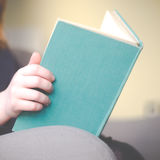 Child Reading Book At Home. Girl Reads Book in Armchair Royalty Free Stock Photos