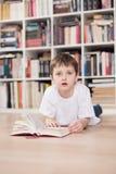 Child reading a book at home. Looking at camera. Child reading a book at home. Dressed in a white t shirt and blue jeans. Looking at camera stock photo