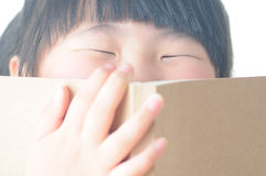 Child Reading Book. Little girl holding a book on the face stock photos