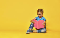 Child is reading a book. Little child is reading a book. Kid on the background of bright color wall. Education and success concept. Yellow, red and  blue Stock Photography