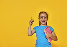 Child is reading a book. Little child is reading a book. Kid on the background of bright color wall. Education and success concept. Yellow, red and  blue Royalty Free Stock Photos