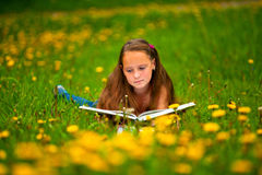 Child reading a book while lying Stock Photos