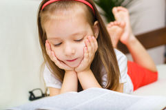 Child is reading book while lying  on a couch Royalty Free Stock Photography