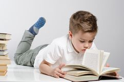 A child is reading a book lying stock images