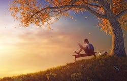 Child reading the book near tree Stock Photos