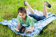 Child reading a book outdoor Stock Photo